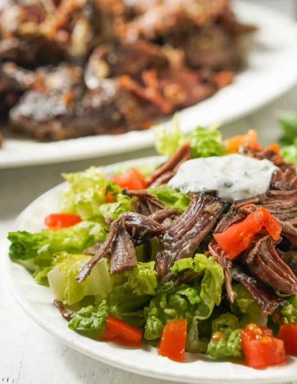 white plate with lamb salad and a platter of roasted lamb in the background