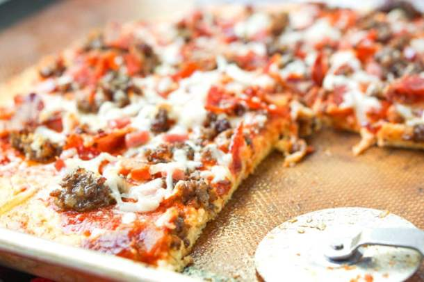 closeup of meat lover's low carb pizza cookie tray with pizza cutter