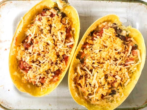 baking dish with 2 halves of spaghetti squash stuffed with Mexican casserole and topped with cheese before baking