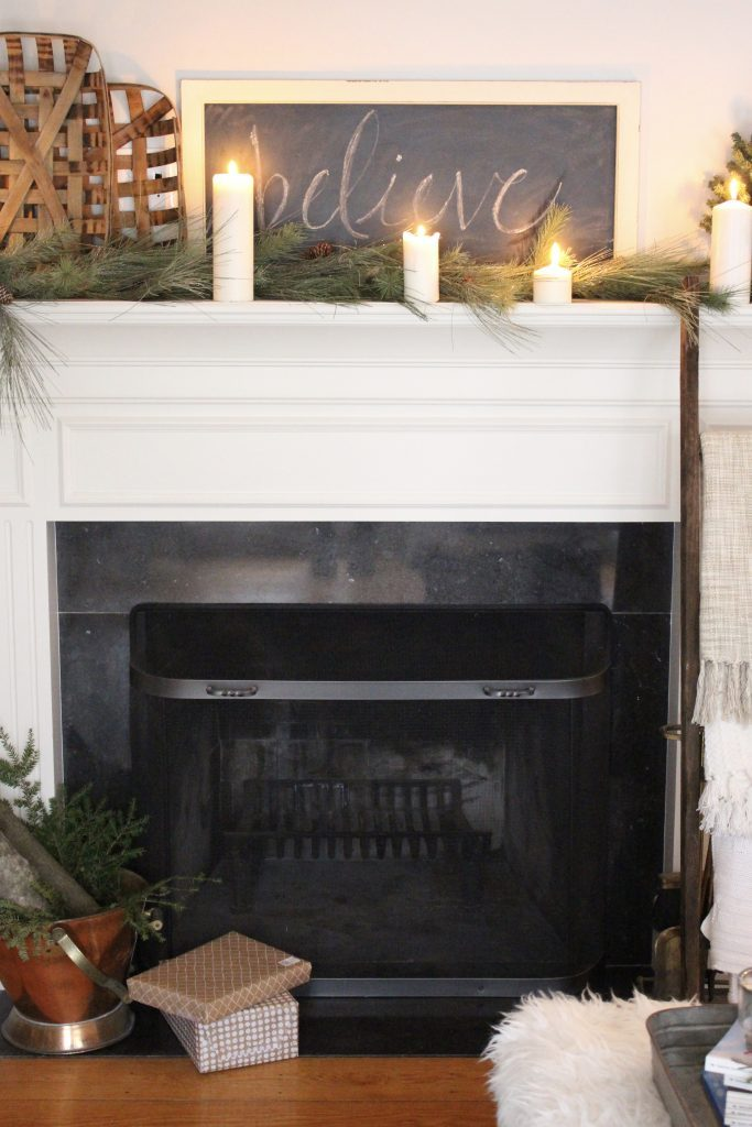 A farmhouse Christmas Mantel dressed in candlelight- home decor- holiday- mantel decor- Do it Yourself- DIY DIY projects- candlelight mantel- living room decorating ideas- room design- rustic home decor- decoration ideas- candlelight and greenery mantel- chalkboard script- winter mantel- candlelight- farmhouse Christmas ideas