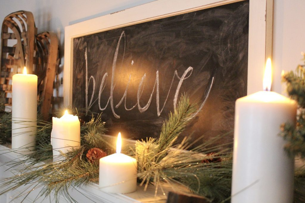 A farmhouse Christmas Mantel dressed in candlelight- home decor- holiday- mantel decor- Do it Yourself- DIY DIY projects- candlelight mantel- living room decorating ideas- room design- rustic home decor- decoration ideas- candlelight and greenery mantel- chalkboard script- winter mantel- candlelight- farmhouse Christmas ideas- decor