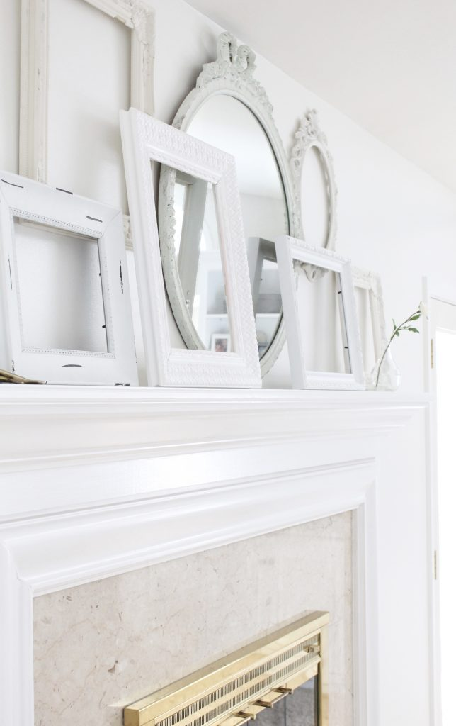 A shabby chic white mantel- layered frames- white mirror- all white decor- romantic design- fireplace decor- mantel decor- home design- decor ideas- mantles- french country style mantel- DIY- Do it Yourself- DIY projects- room design- wall decorating ideas- gallery wall- room decor ideas- decoration ideas- farmhouse style