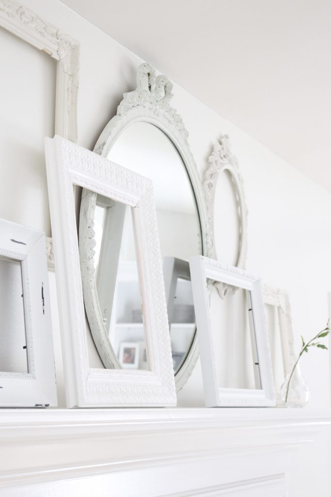 A shabby chic white mantel- layered frames- white mirror- all white decor- romantic design- fireplace decor- mantel decor- home design- decor ideas- mantles- french country style mantel- DIY- Do it Yourself- DIY projects- room design- wall decorating ideas- gallery wall- room decor ideas- decoration ideas- farmhouse style chandelier- romantic style