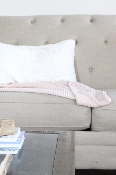 Spring Family Room- Spring Decor- Blush Tones- Pink- Adding spring decor- home design- DIY- decorating ideas for spring- pastel decor- spring- seasonal decor- family room- living spaces- wall decorating ideas- fireplace decor- tufted couch