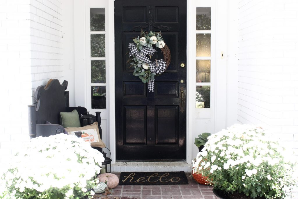 White brick ranch home decorated outdoors for fall- small porch decor- fall decorating outdoors- porch decor- fall porch decor- autumn- small porch- handmade wreath- gingham- mums- pumpkins- black and white outdoor decor- handmade pillow