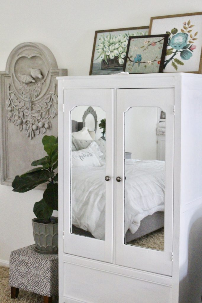 White Cottage Master Bedroom- gray- white- green- shabby chic bedroom- farmhouse decor- layered mirrors- painted gray furniture- DecoArt- Repose Gray- white bedding- white painted furniture- Armoire- fireplace in the bedroom- home design- large bedroom space- sitting area in the bedroom- bookshelves in a bedroom- layered art pieces