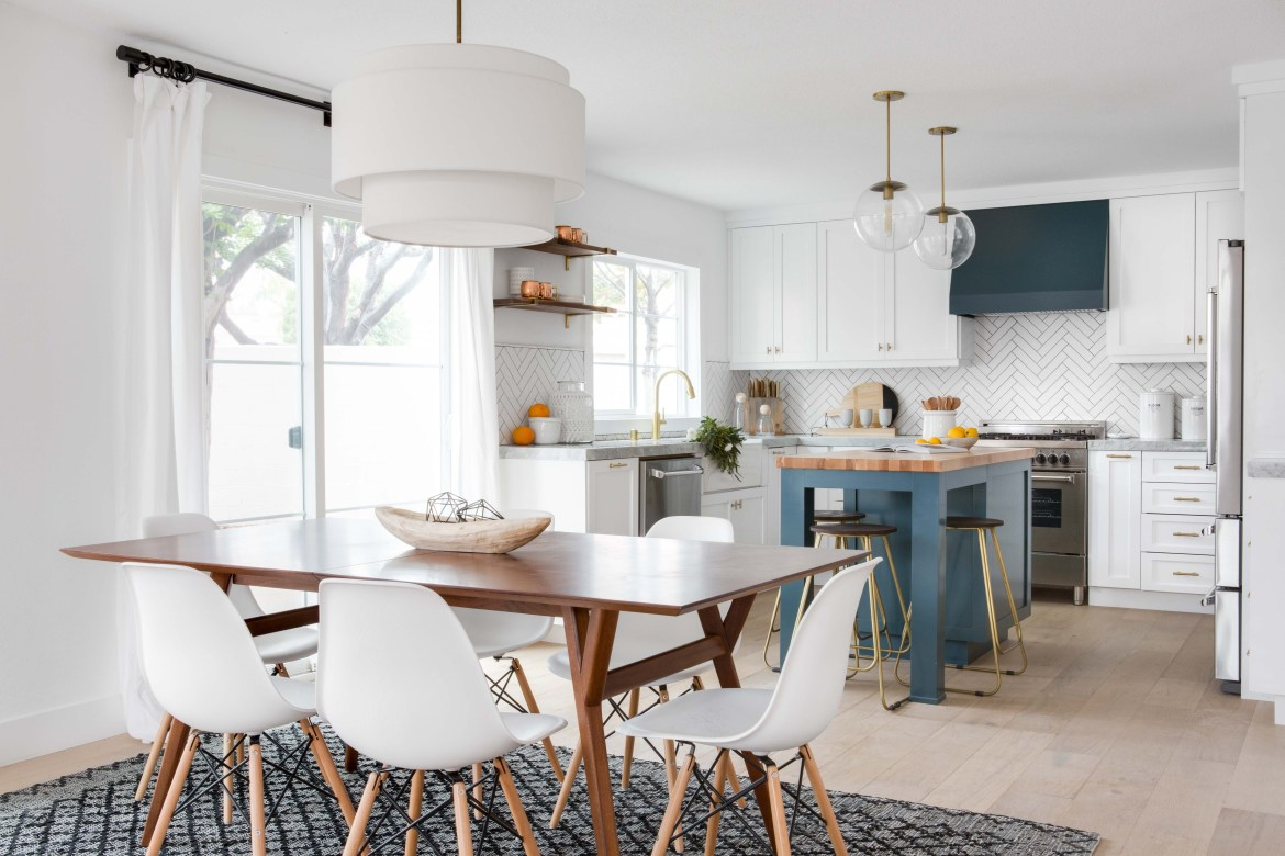 White fabric shade pendant light over table and glass pendant lights over kitchen island