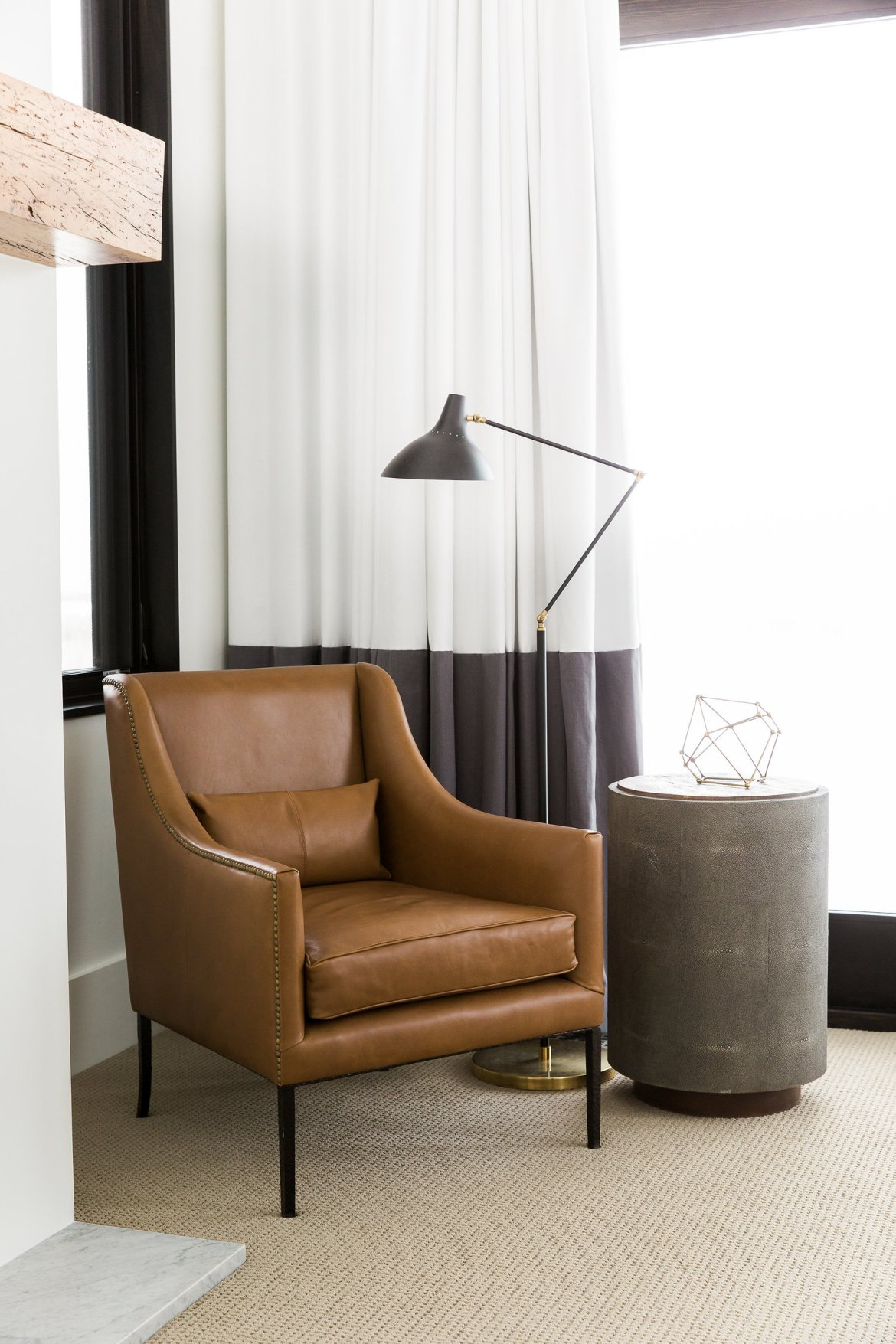 Modern style master bedroom corner with accent chair and floor lamp.