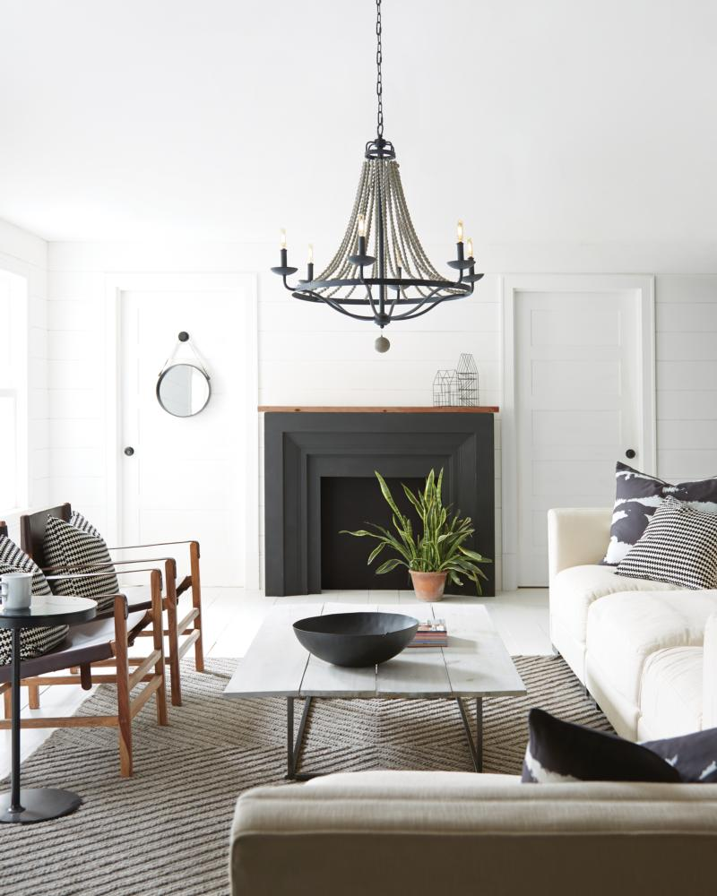 Modern farmhouse living room with beaded chandelier, fireplace, furniture, area rug, coffee table , and wall panelling.