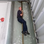 Photo by Dave Warner - even though the firemen's sliding poles stopped being used in 2007, firefighter Chad Malley shows he can still make the climb.
