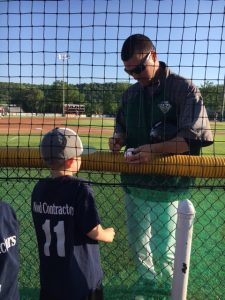 Photo submitted - Cory Haggerty signs a baseball for one of the young fans at a game.