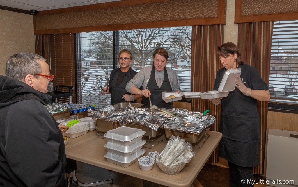 Photo by Dave Warner - Alpine Rehabilitation staff members (L to R) Casey, Mary and Sandy, serve up a chicken & biscuits dinner for a customer.