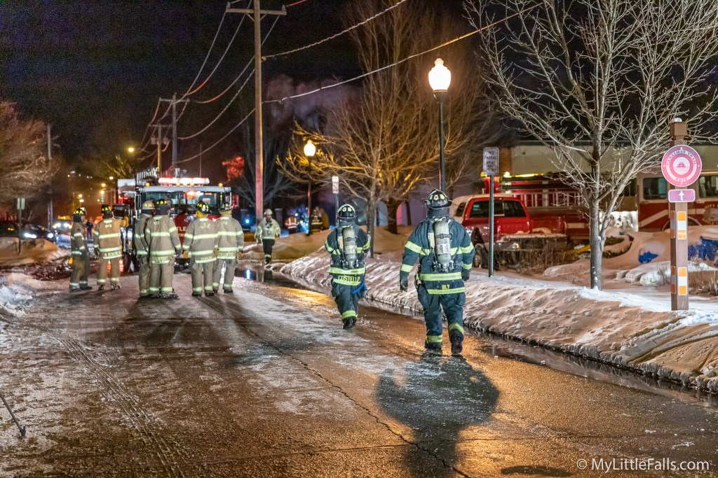 Photo by Dave Warner - Firefighters walk along Southern Ave in Little Falls while fighting a fire at PEMS Tool & Machine, Inc.