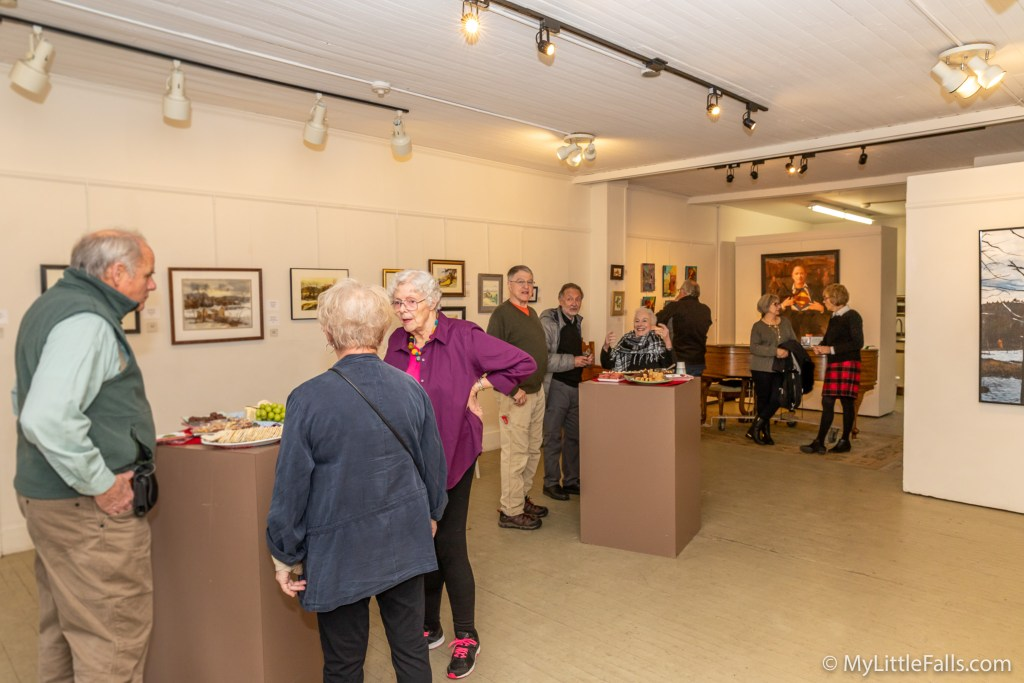 Photo by Dave Warner - Visitors spend some time chatting and looking at the artwork during the Faculty/Student Art Show closing reception.
