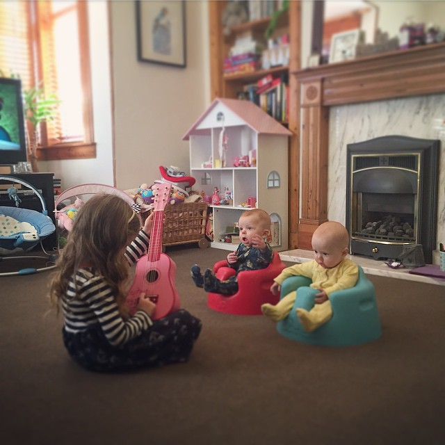 30/365 She's such a beautiful big sister. Today she was teaching the babies how to play guitar. I think Harrys got it....
