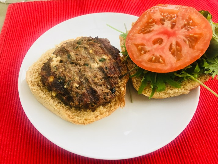 Feta and basil Burger on bun with lettuce and tomato