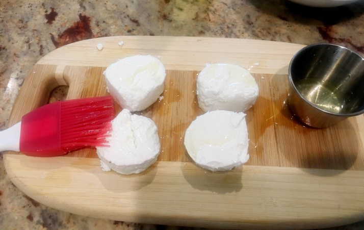 Coat both sides of the goat cheese with olive oil.