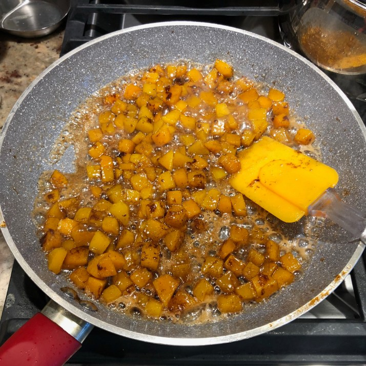 add in drained butternut squash mix until thoroughly coated in sauce. photo of squash in skillet with the butter and sugar sauce