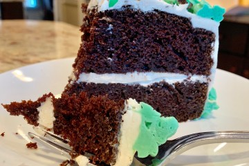 a slice of chocolate irish cream cake decorated with green piped icing and chopped green m&m's