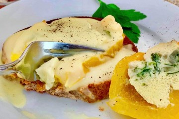 Sliced egg-stuffed pepper on toast covered with hollandaise sauce