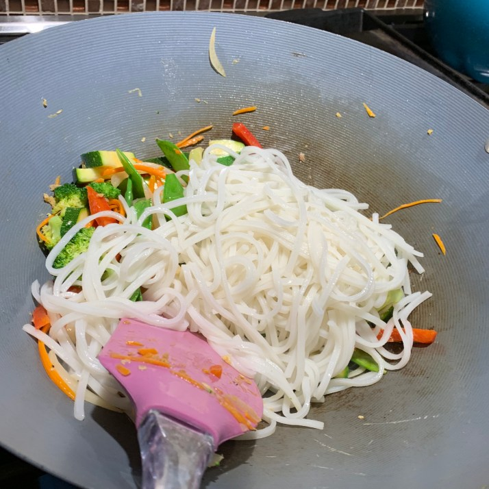 add rice noodles to the wok and mix well