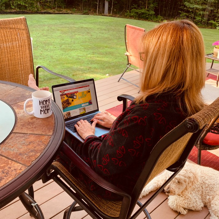 Susan sitting at her patio table ordering groceries in her PJ's. with coffee.