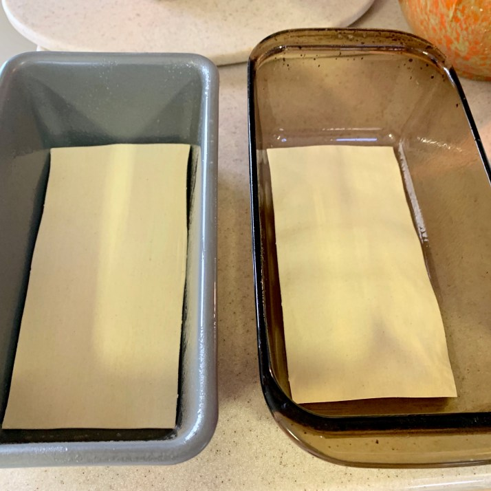 "start by spraying a loaf pan with cooking spray and place one noodle at the bottom of two 4""x4"" loaf pans  photo of loaf pans with one no boil lasagna noodle in the bottom of each pan"