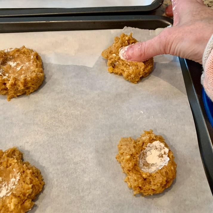 using your thumb dusted with flour, make a thumbprint in the center of the cookie