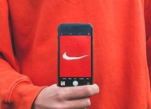 Person holding smart phone with photo of embroidered Nike swoosh