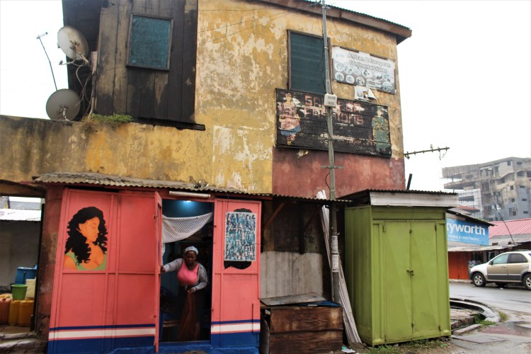A colourful building in old Accra on the outskirts of Makola Market. A lady who owns a wig and braiding store is about to step out of her shop.