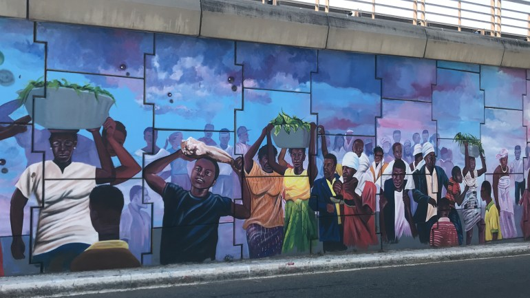 Ghana street art - Murals at the Ako Adjei interchange Accra Ghana depicting people carrying bowls of libation at local Ghana festivals