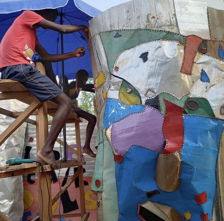 Ghanaian Artist Tei Huagie and his sons work on the street art 'National Inspiration' in Accra Ghana