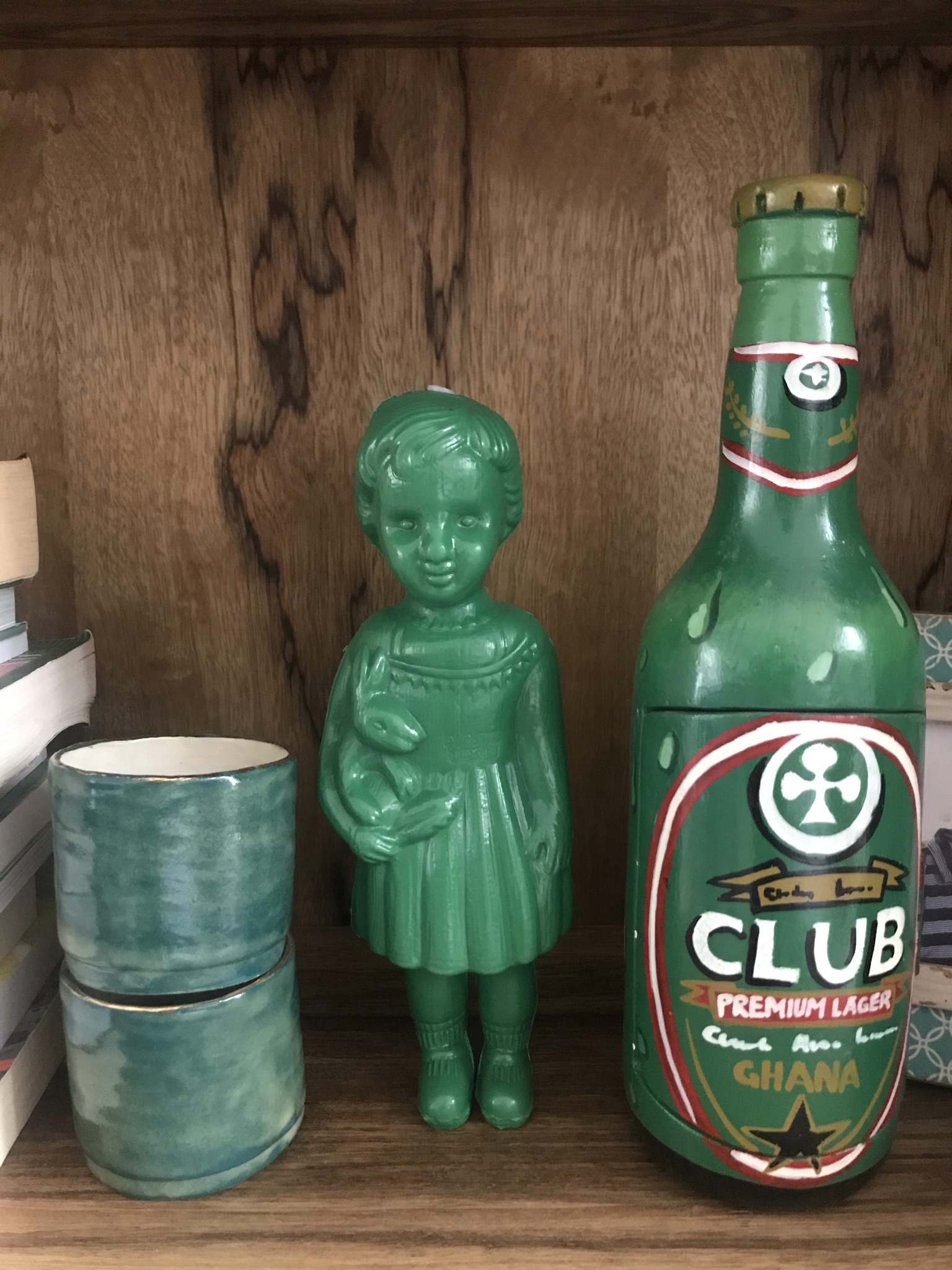 A green plastic Clonette Doll stands on our bookshelf next to a wooden mimic of a Ghanaian fantasy coffin in the shape of a Club beer bottle.