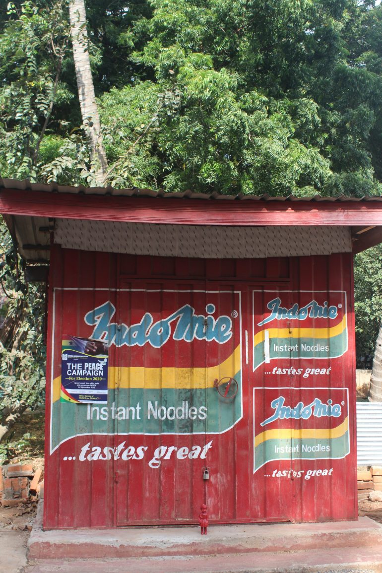 A Red Clonette doll stands in front of a kiosk advertising Indomie instant noodles in Accra Ghana
