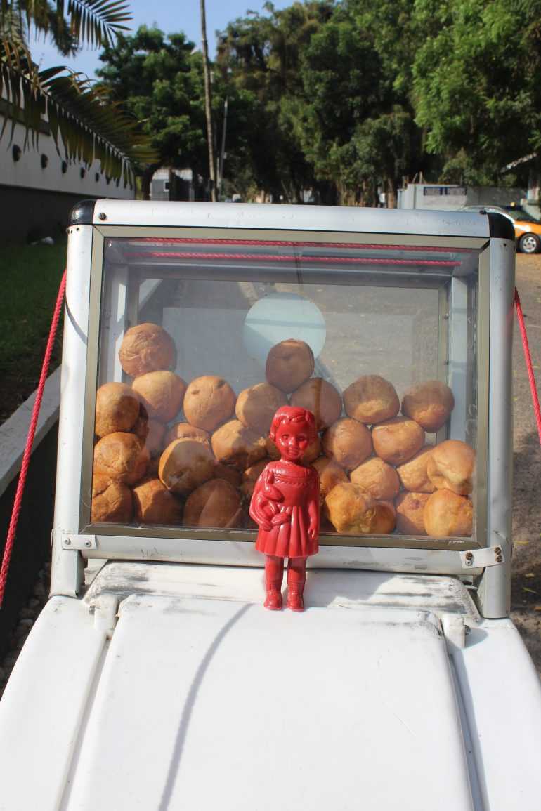 A Red Clonette doll stands in front of a bike selling bofrot in Accra Ghana