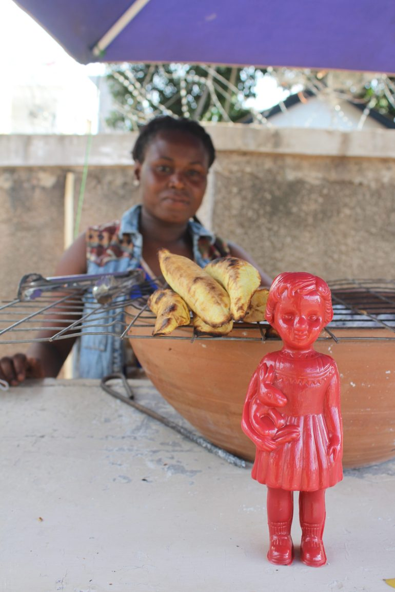 Red Clonette doll in Accra Ghana with a lady selling plantain