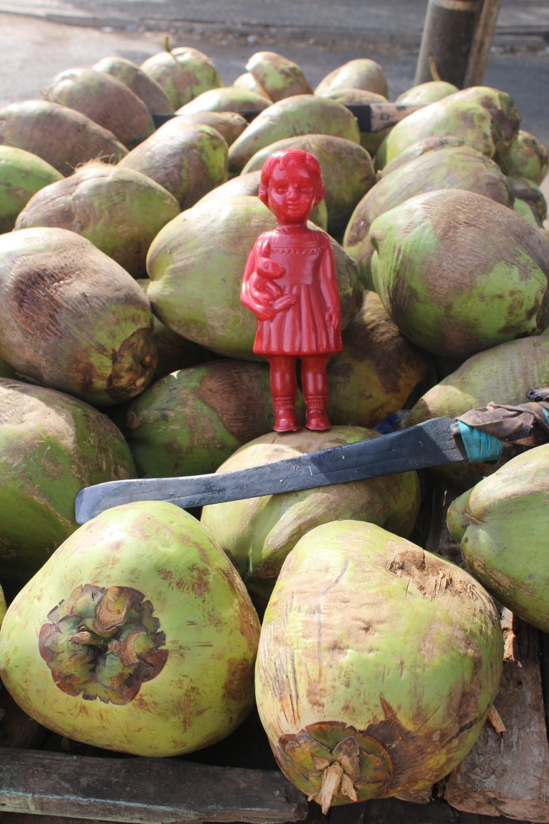 Red Clonette doll in Accra Ghana amongst coconuts