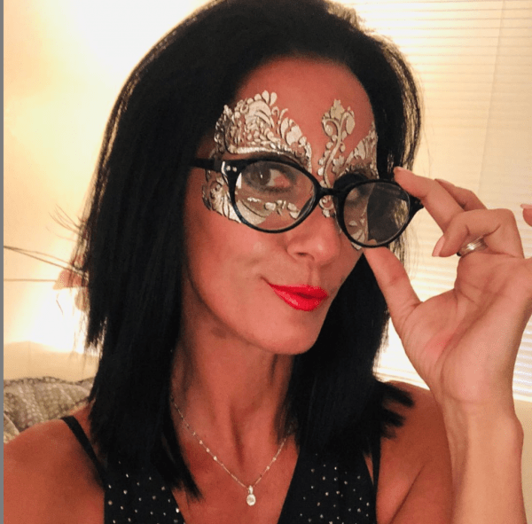 silver foil masquerade mask on woman with glasses