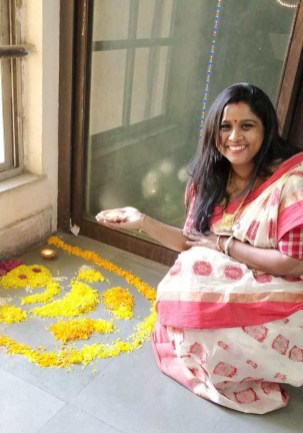Shoma decorating the office with a rangoli for Diwali