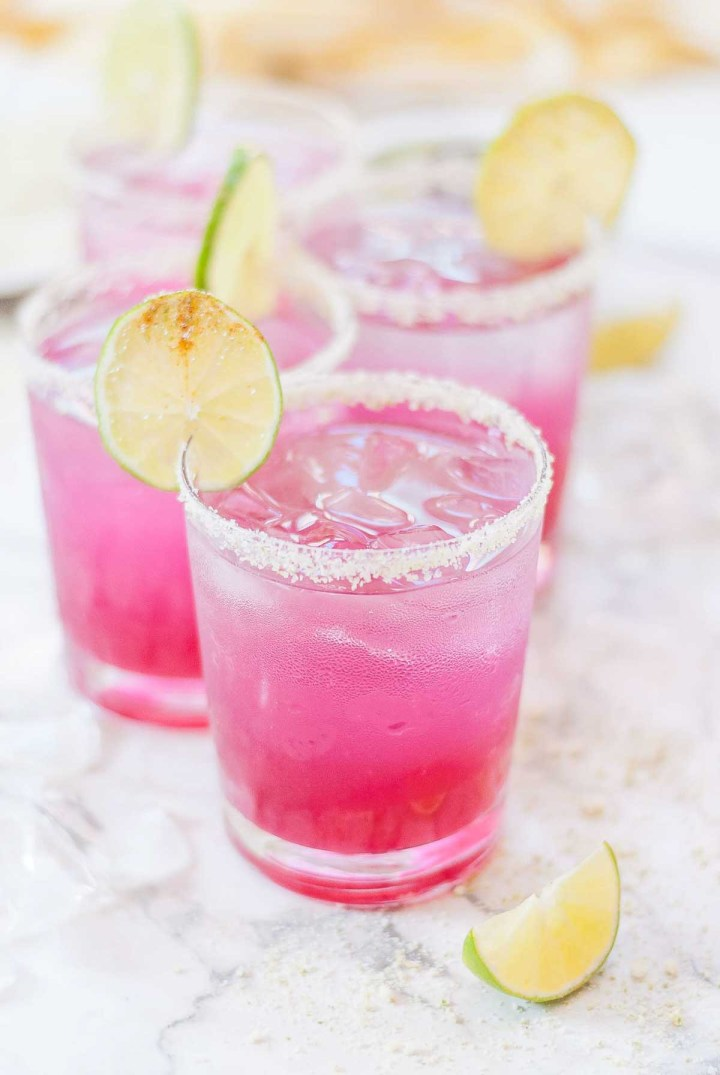 Close up image of four salt-rimmed glasses filled with a hot pink drink and topped with lime slices