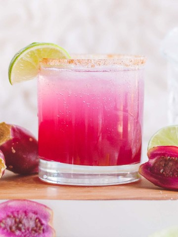 A hot pink cocktail in a glass topped with a lime wedge garnish