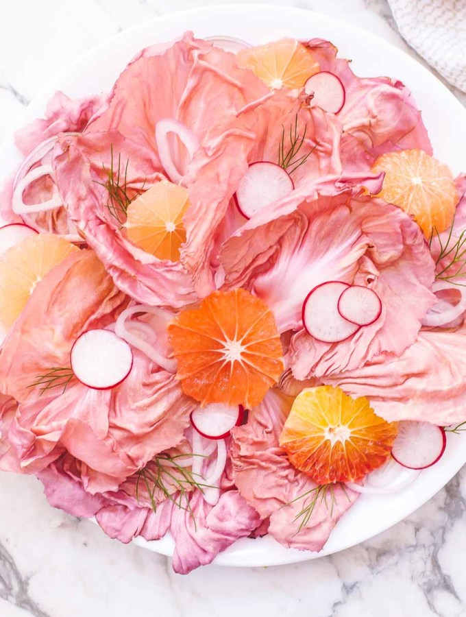 Pink radicchio salad in a circle with orange and radish slices