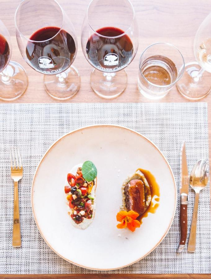 white lunch plate with lamb and vegetables, silverware on the side and wine glasses above filled with red wine