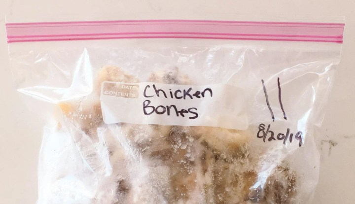 A sealed, labeled, and dated plastic bag filled with a frozen chicken carcass.