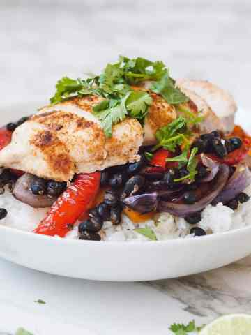 Sliced chicken in a white bowl on top of black beans, red peppers, and rice.