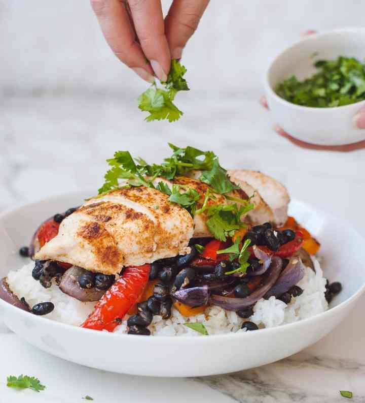 Hand topping cilantro over a sliced chicken breast in a white bowl.