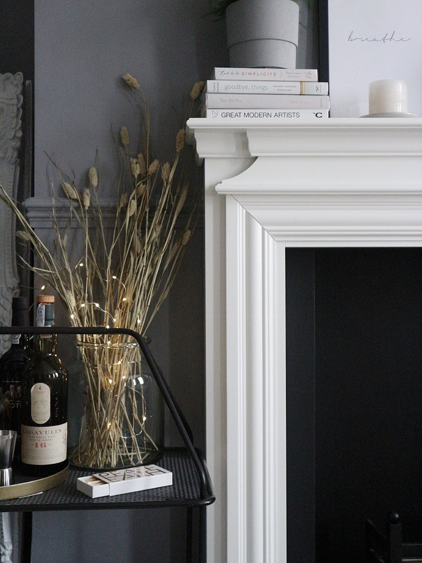 close up fireplace grey neutral colours monochrome fairy lights dried flowers