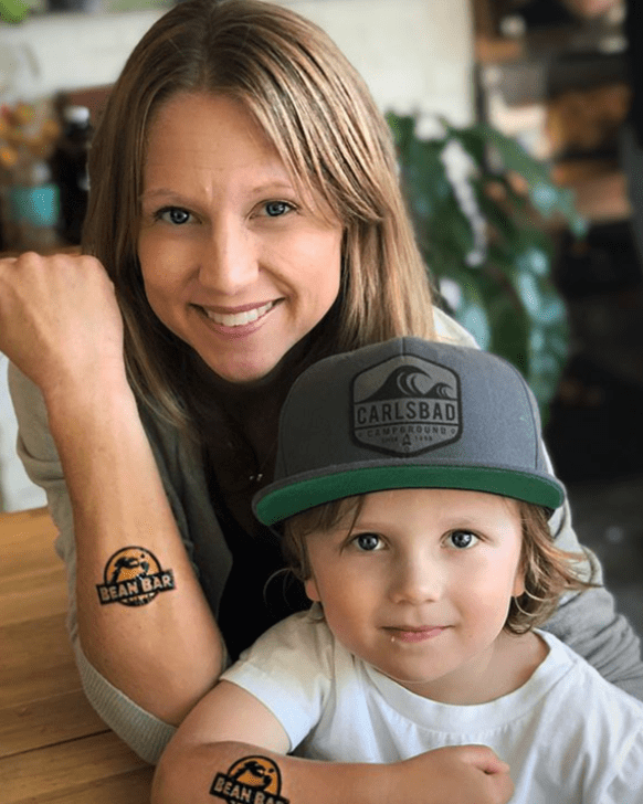 happy mom and son in coffee shop with tattoos