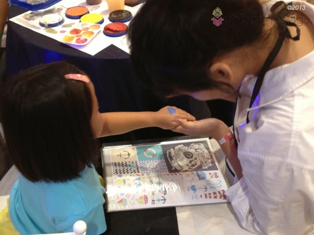 Hand-painting nautical shapes at the launch.