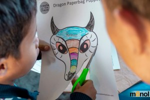 Child cutting a dragon drawing